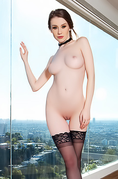Emily Bloom is posing by the window