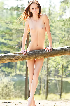 Cute babe is posing naked by the lake
